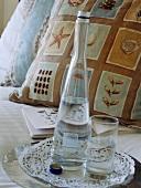 Tablett mit Wasserglas und Wasserflasche auf dem Bett mit gemusterten Kissen