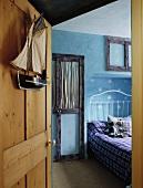 Blick durch Kiefernholztür in Kinderschlafzimmer auf weisses Metallbett mit Teddy und Muster in Schablonentechnik auf hellblauer Wand