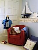Kinderzimmer im maritimen Stil mit Segelboot auf gemauerter Ablage mit Segelboot-Bordüre und rotem Clubsessel mit Teddy