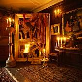 Raumhohe Skulptur aus leeren, vergoldeten Bilderrahmen stimmungsvoll mit Kerzenlicht beleuchtet in Wohnraum mit Holzvertäfelung