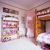 Grosses Barbie-Puppenhaus und rustikales Hochbett in Kinderzimmer mit weissen Dielen und rosafarbener Tür