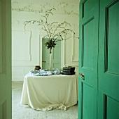 Blick durch offene türkisfarbene Kassettentür in georgianisches Esszimmer mit floralem Stuck an den Wänden und stoffdrapiertem Tisch