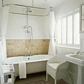 Landhaus-Badezimmer mit weißem englischen Korbstuhl neben Badewanne mit Klauenfüssen und Vorhang an ovaler Brausestange