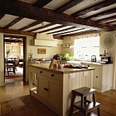 Cremefarbene Landhausküche mit Kochinsel unter dunkler Holzbalkendecke mit Blick in angrenzendes Wohnzimmer