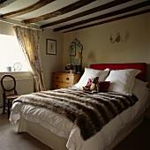 Doppelbett mit Webpelzdecke und Teddy in niedrigem Landhaus-Schlafzimmer mit Holzbalkendecke