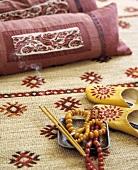 Nahaufnahme von Gebetsketten und brennenden Räucherstäbchen vor rosafarbenen Kissen auf gemustertem Sisalteppich