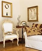 Eingerahmte Stammes-Ketten hängen über einem geschnitzten antiken Stuhl und einem Sofa in der Ecke des italienischen Wohnzimmers