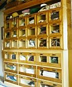 Alter Kleiderschrank aus Holz, die einzelnen Fächer mit Glasfronten