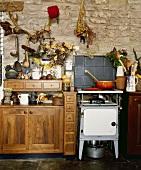 Ein altmodischer Ofen in einer Landhausküche mit hölzernen Schränken und Steinmauern