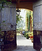 Blick durch geöffnete Doppeltür in einen toskanischen Garten im Sommer