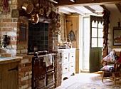 Ein Holzofen in gemauertem Kamin in einer Landhausküche