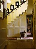 Eine Diele mit weihnachtlich dekoriertem Treppengeländer und weisser Paneelwand unter der Treppe