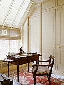 Altmodischer Schreibtisch mit gepolstertem Stuhl neben Einbauschrank im Dachgeschoss