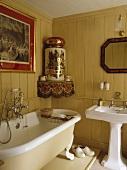 Großer antiker Topf auf Eckregal über freistehender Badewanne im neutral getäfelten Badezimmer mit weißem Sockel Becken