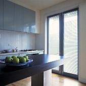 Ein Teller mit Äpfeln steht auf einer grauen freistehenden Arbeitsplatte in einer hellgrauen Küche mit einem Flügelfenster, das zu einer Terrasse führen und an dem Jalousien angebracht sind