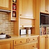 Ein Toaster und ein Mixer stehen in einem Küchenschrank mit einer Tür, die man hochklappen kann