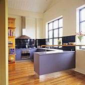 Violette Einbauschränke und Arbeitsflächen in einer modernen weißen Küche mit einen hellen Parkettboden