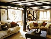 In einem Fachwerkhaus stehen zwei cremefarbigen Sofas vor einen Ledersitztisch
