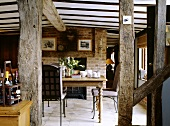 Ein ländliches Esszimmer mit einer Balkendecke und Ziegelwände