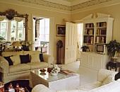 Cremefarbiges Sofa und ein Bücherregal richten ein traditionelles und schlichtes Wohnzimmer ein