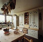 Geschnitzte grau lackierte Wandschränke stehen in einer ländlichen Küche mit einem alten Kiefern Tisch und Stühlen