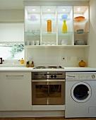 Ein Chrombackofen und eine weiße Waschmaschine stehen unter einer beleuchteten Vitrine aus Holz und Glas, die mit farbigen Vasen und Geschirr eingedeckt wurde