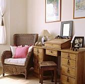 Pinke und weiße Kissen liegen auf einen Korbsessel, der neben einen alten Kiefer-Schreibtisch steht