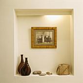 Ein altes schwarz-weiß Foto hängt in einer beleuchteten Nische, auf der zwei braune Glasflaschen und ein Specksteinbehälter stehen