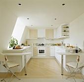 In einer modernen Küche im Dachgeschoss stehen jeweils links und rechts davon Frühstück Bars und Metall-Holzstühle mit weißen Sitzpolstern