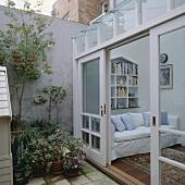 Ein moderner Wintergarten mit offenen Glasschiebetüren, die in den kleinen Innenhof führen