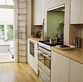 Helle, schlicht-moderne Einbauküche mit hoher Stahlleiter neben Durchgang zum abgesenkten Wohnraum