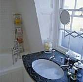 Schwarzer Marmorwaschtisch mit gefülltem Unterbaubecken und altmodischen Armaturen vor Sprossenfenster in weißem Bad