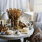 Getrocknete Rosen in einer Vase auf weißem Tischchen mit Sammlung von Elfenbeindosen und Parfümflaschen vor Spiegel in Badezimmer