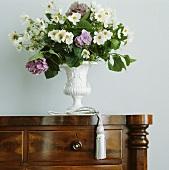 Nahaufnahme eines weiss-violetten Blumenstrausses in weisser Amphorenvase auf antiker Holzkommode