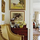 Gerahmte Gemälde über antiker Holzkommode in Wohnraum mit antiken Sesseln verschiedener Epochen