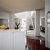 Weisser Küchenunterschrank mit Marmorplatte in modernem offenen Wohnraum mit offener weisser Holztreppe und glänzendem Holzparkett