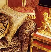 Nahaufnahme von Seidenkissen auf Sofa mit Animalprint neben vergoldeter Figur als Lampenfuss