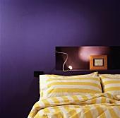 Gelbweiss gestreifte Bettwäsche vor beleuchteter Nische in lilafarbener Wand mit gerahmtem Bild