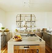 Moderne Edelstahlküche mit Kochinsel und Geschirrablage aus Metallgitter über Spüle