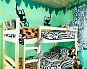 Bettwäsche mit Tierfell-Motiv und Kuscheltiere auf hölzernem Etagenbett in Kinderzimmer mit grünem Dschungel-Wandbild