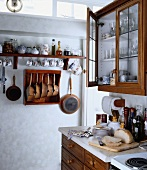 Traditionelle Küche mit aufgehängten Tassen, Töpfen, Pfannen und einfachen Schränken mit Holzfront