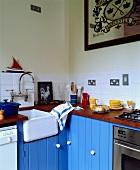 Weisses Keramikspülbecken mit altmodischer Armatur zwischen strahlend hellblauen Einbauschränken