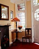 Raumecke im Stil Edward VII mit Bleiglasfenstern und Art-Nouveau-Lampe mit Bleiglasschirm auf Holztischchen