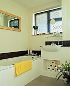Helles Bad mit schmalem Streifen aus dunkelgrauen Mosaikfliesen und gemauertem Stauraum unter dem Waschbecken