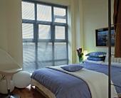Von durchsichtigem, blauem Stoff verhangenes Fenster in modernem Schlafzimmer mit Bettzeug in Hellblau und Weiss