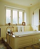 Badewanne mit cremefarbener Holzverkleidung, Granitumrahmung und altmodischer Messingarmatur in der Mitte eines hellen Badezimmers