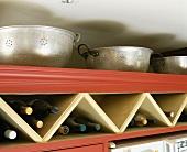 Alte Küchensiebe aus Aluminium über Dreiecksregal mit Weinflaschen