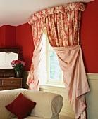 Offen drapierte, rot-weisse Toile-de-Jouy Vorhänge vor satt roter Wand und antike Frisierkommode aus dunklem Holz