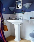 Säulenwaschbecken vor weiss-blauer Wand mit Spiegel und Lampenpaar in traditionellem Badezimmer