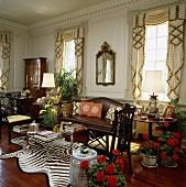 Ein Glastisch auf einem Zebrafell und ein Leder-Kanapee in einem Wohnzimmer mit Zimmerpflanzen